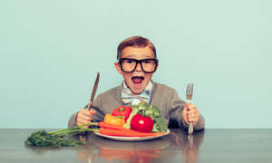 National Nutrition Month boy with glasses ready to eat his vegetables